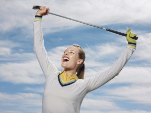 Happy female golfer holding club against sky